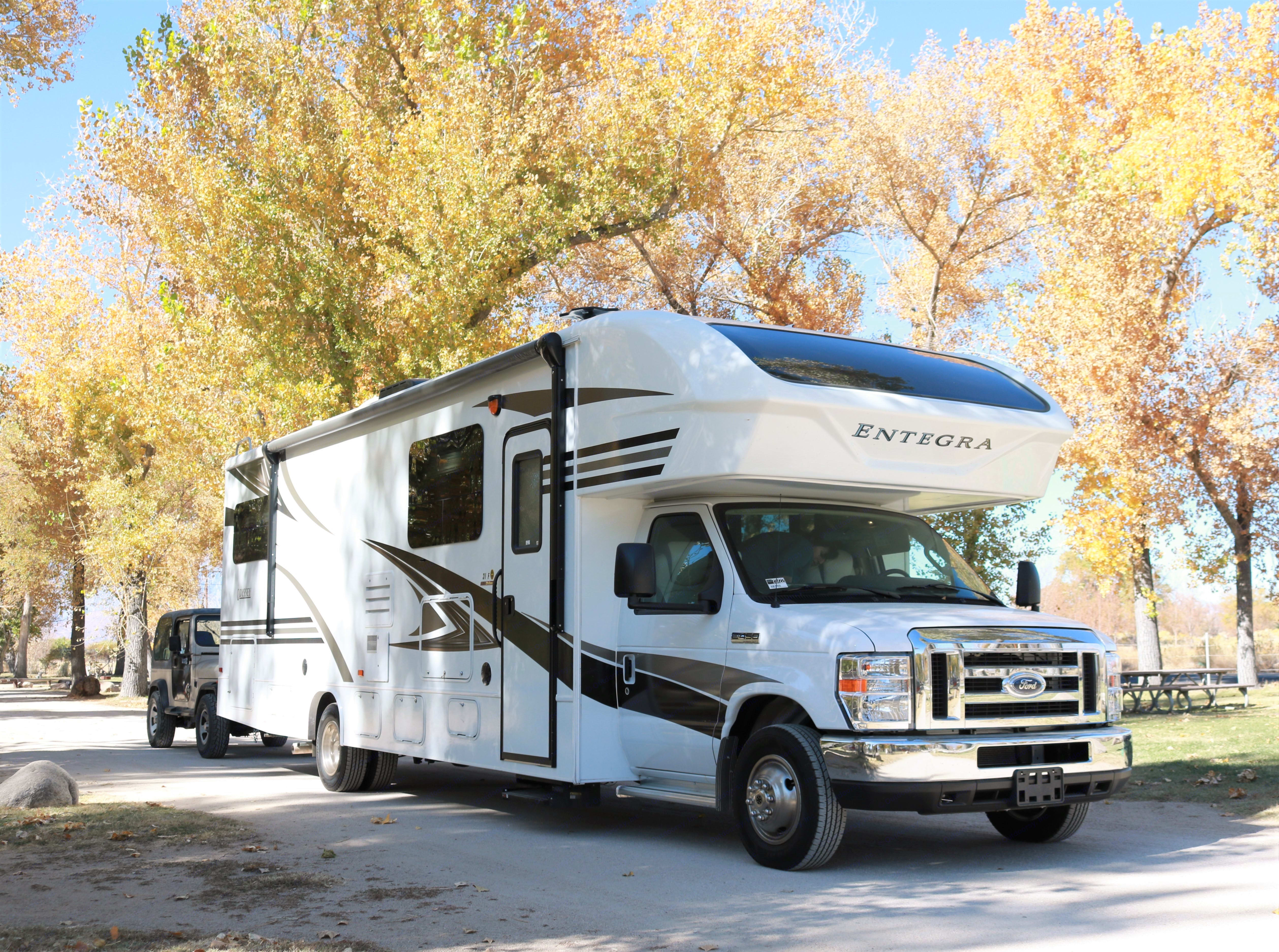 This side shows the side awning and large compartment to left of door is an outside tv.. Jayco Entegra Coach Emblem 2019