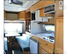 Kitchen has Microwave, 3 way Frig, two burner propane stovetop with ventilation fan. sink with running water.. Roadtrek 190 Popular 1998