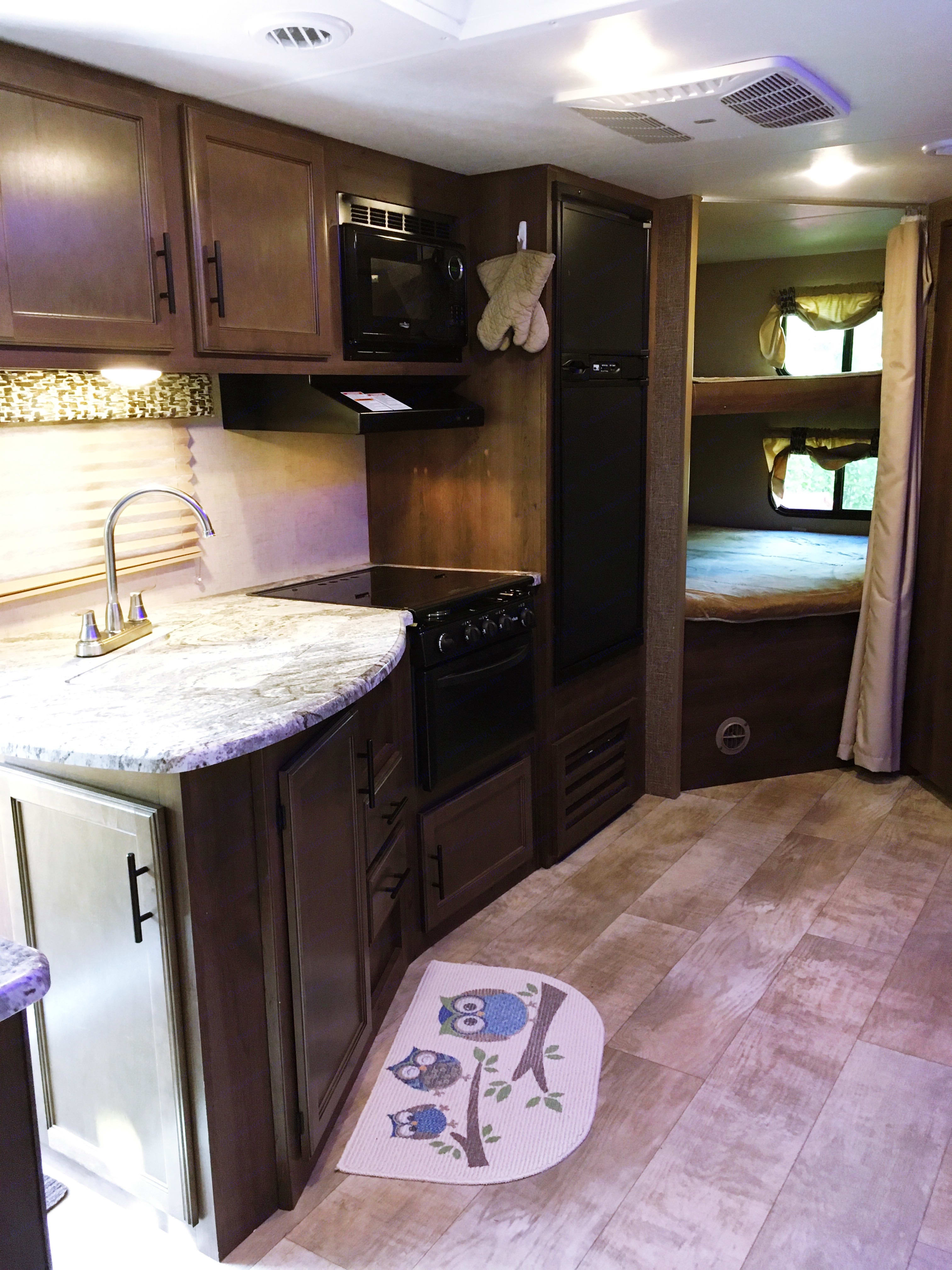 Kitchen area, sink, range and bunk beds. K-Z Manufacturing Connect 2018
