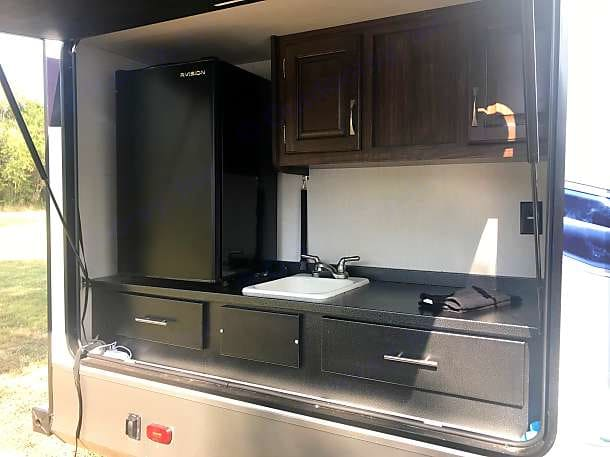 Outdoor kitchen with refrigerator, sink and counter-space. Palomino Solaire Ultra Lite 2019