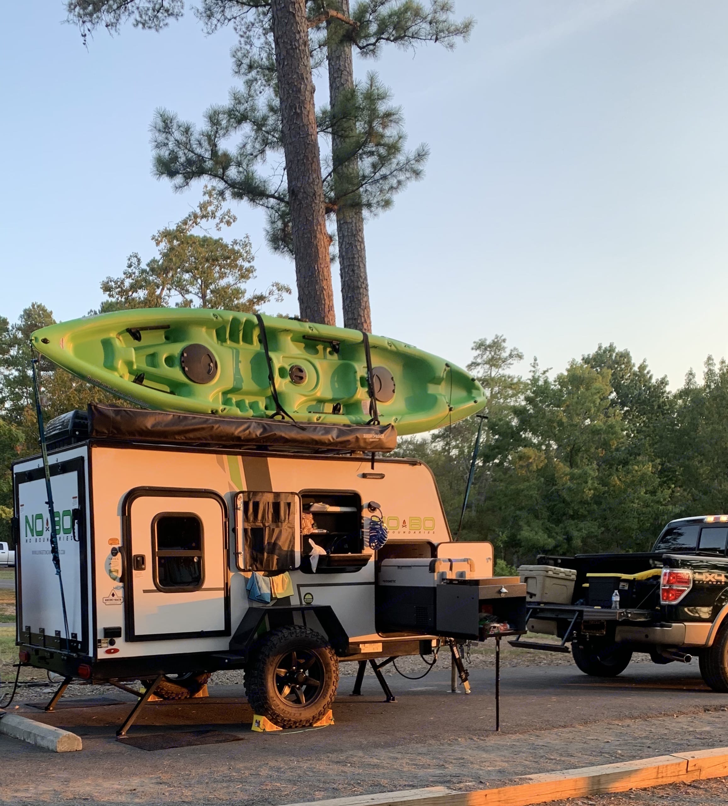 Camper in camp with kitchen open.  Showing the two person kayak in the kayak rack.  Kayak is available for an additional rental fee.. Forest River No Boundaries 10.6 2019