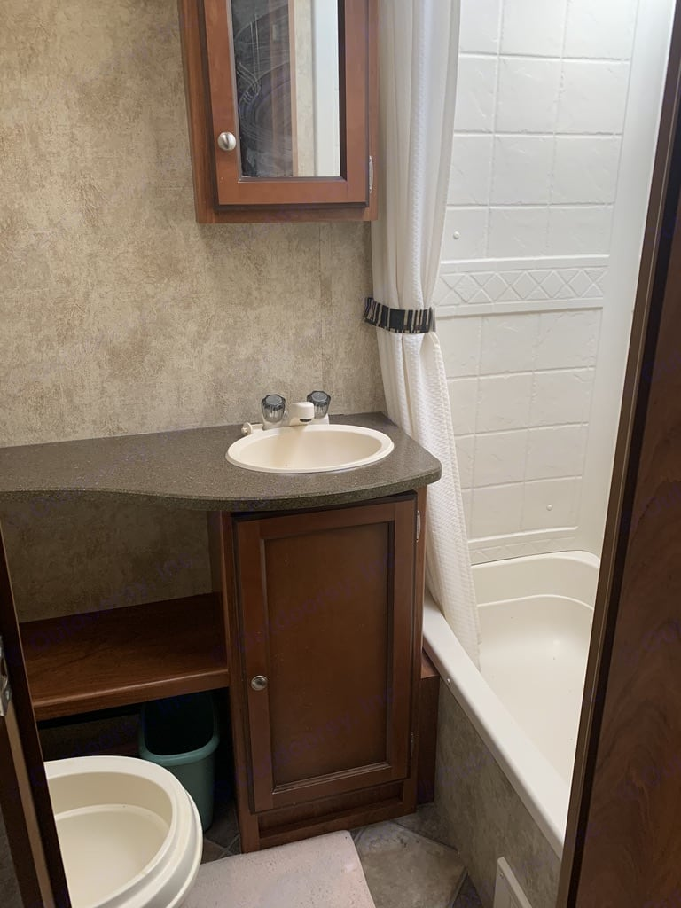 Bathroom with tub/shower, toilet, and sink. Keystone Passport Ultra Lite Grand Touring 2910BH 2012