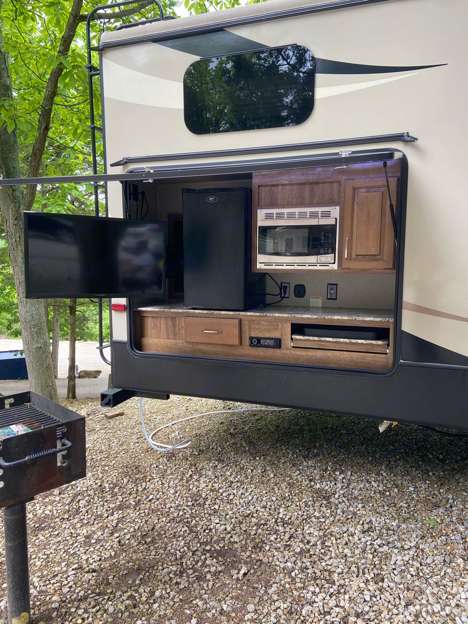 Outdoor kitchen with cooktop, TV/radio, microwave, refrigerator and storage. Keystone Laredo 2019