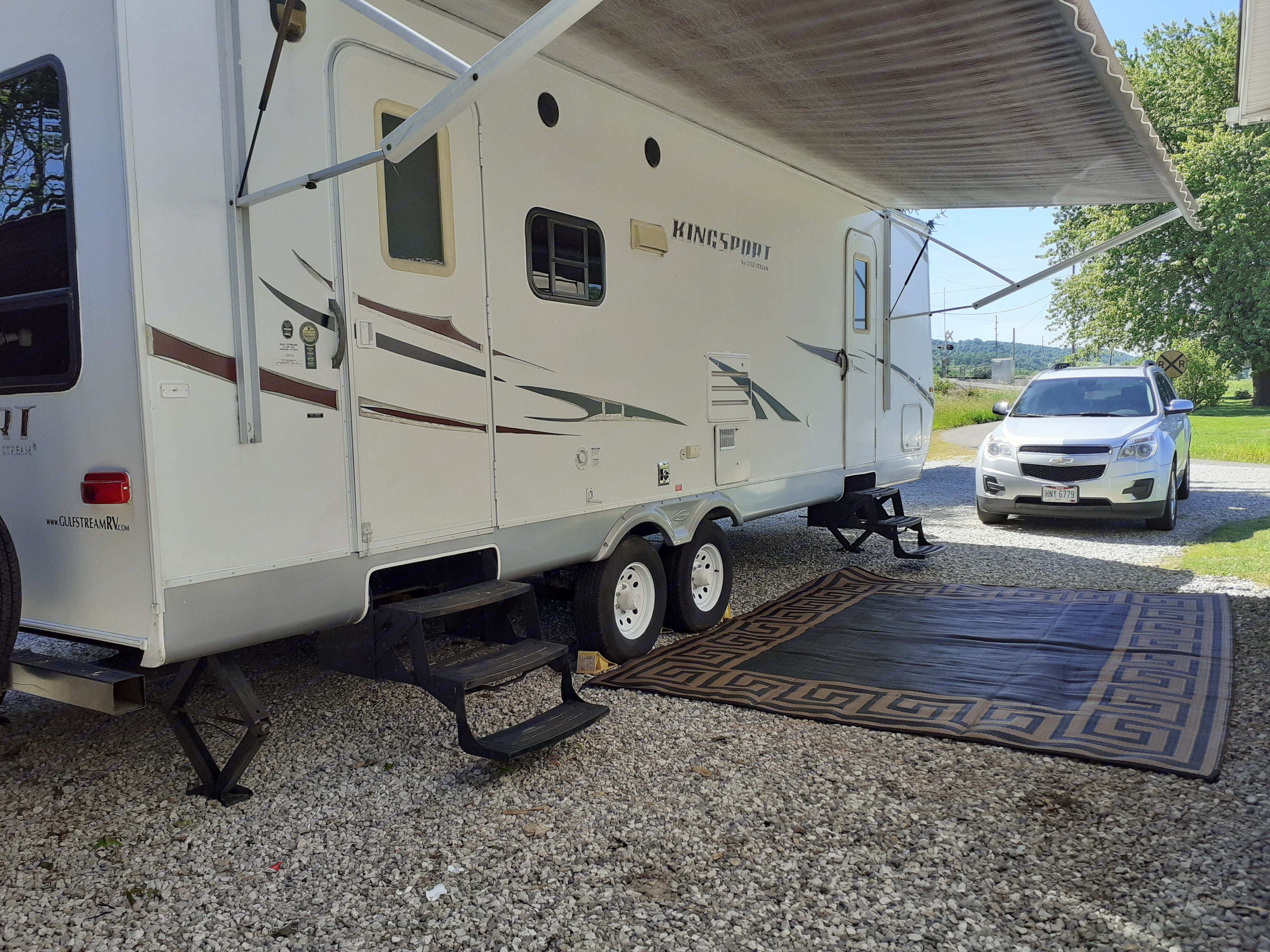 Brown fade electric awning and large patio mat.  Awning lights are included with rental and plug into to outside outlet.. Gulf Stream Kingsport 2010
