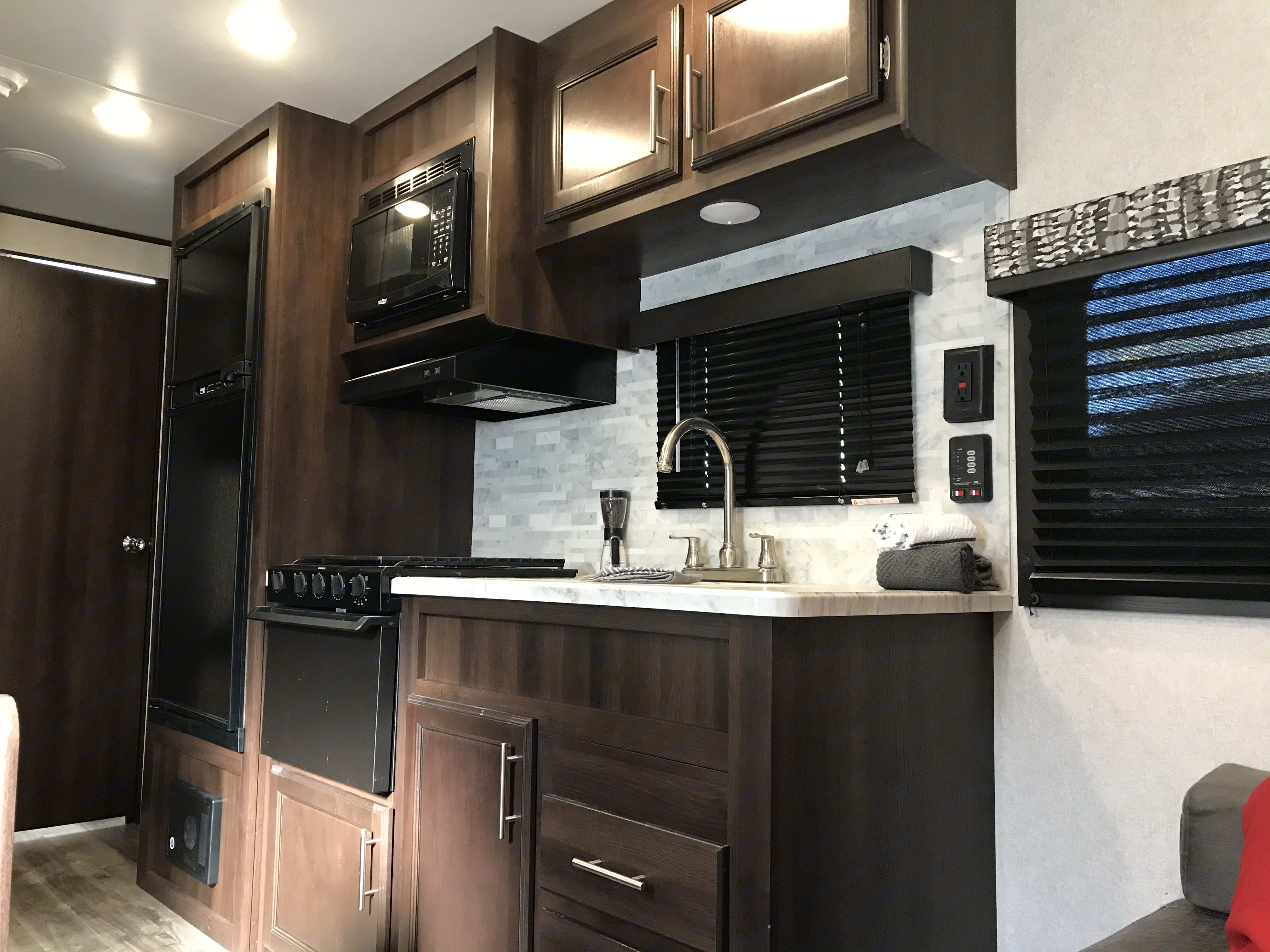 Another pic of the kitchen, expanded view with 6cubic foot refrigerator, 3 burner stone and microwave. Jayco Jay Flight 2020
