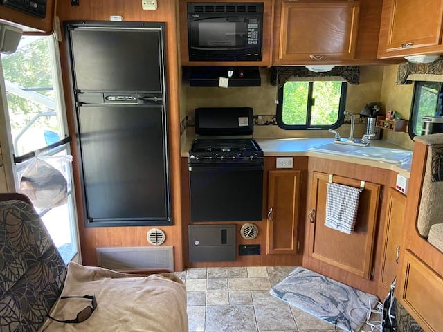 Full kitchen with three-burner stove, large refrigerator and freezer, microwave, and all kitchen supplies. Lance 2285 2011