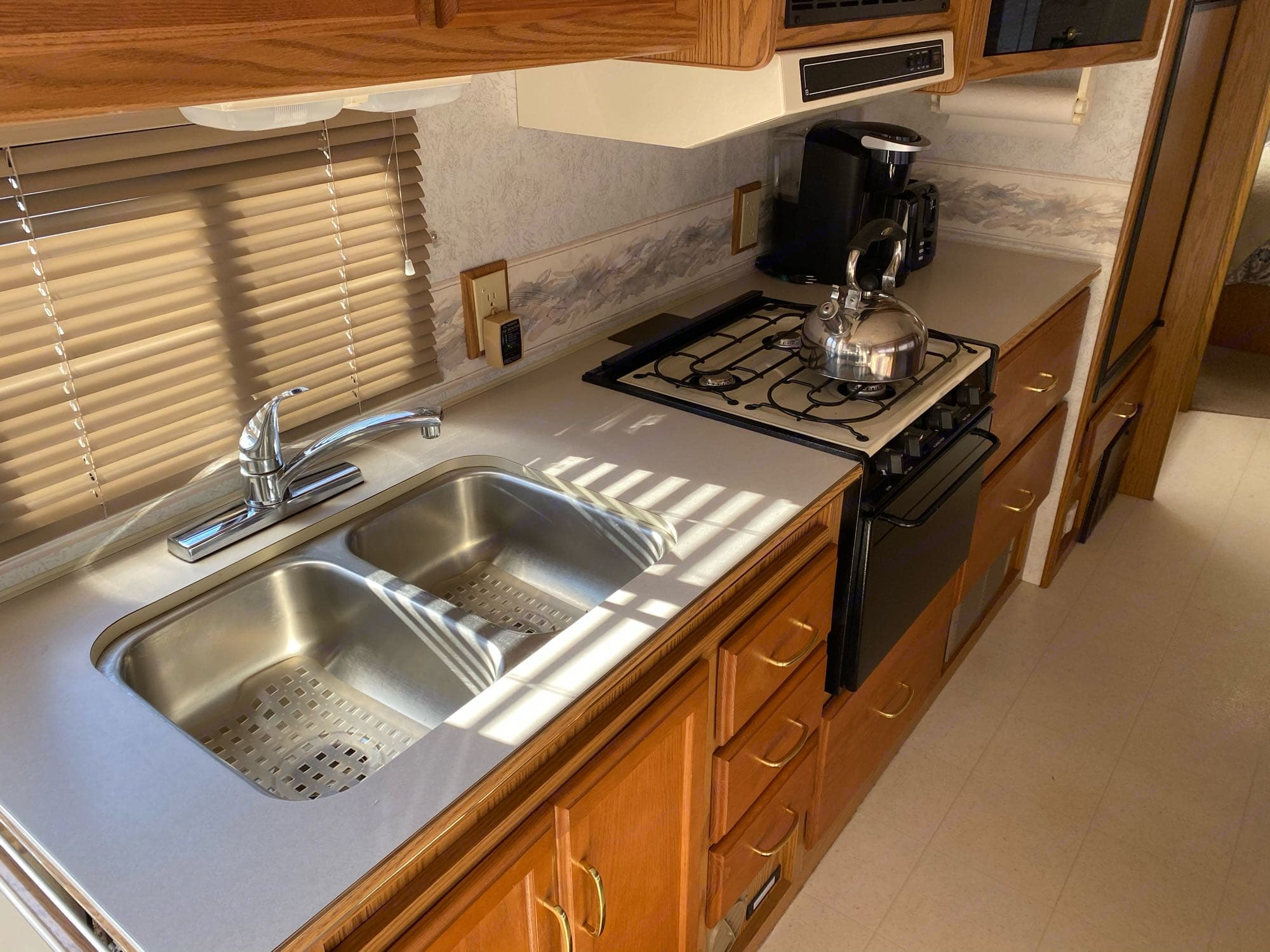 stainless steel sink with 3 burner stove, oven and kureg coffee maker. Itasca Spirit 2000