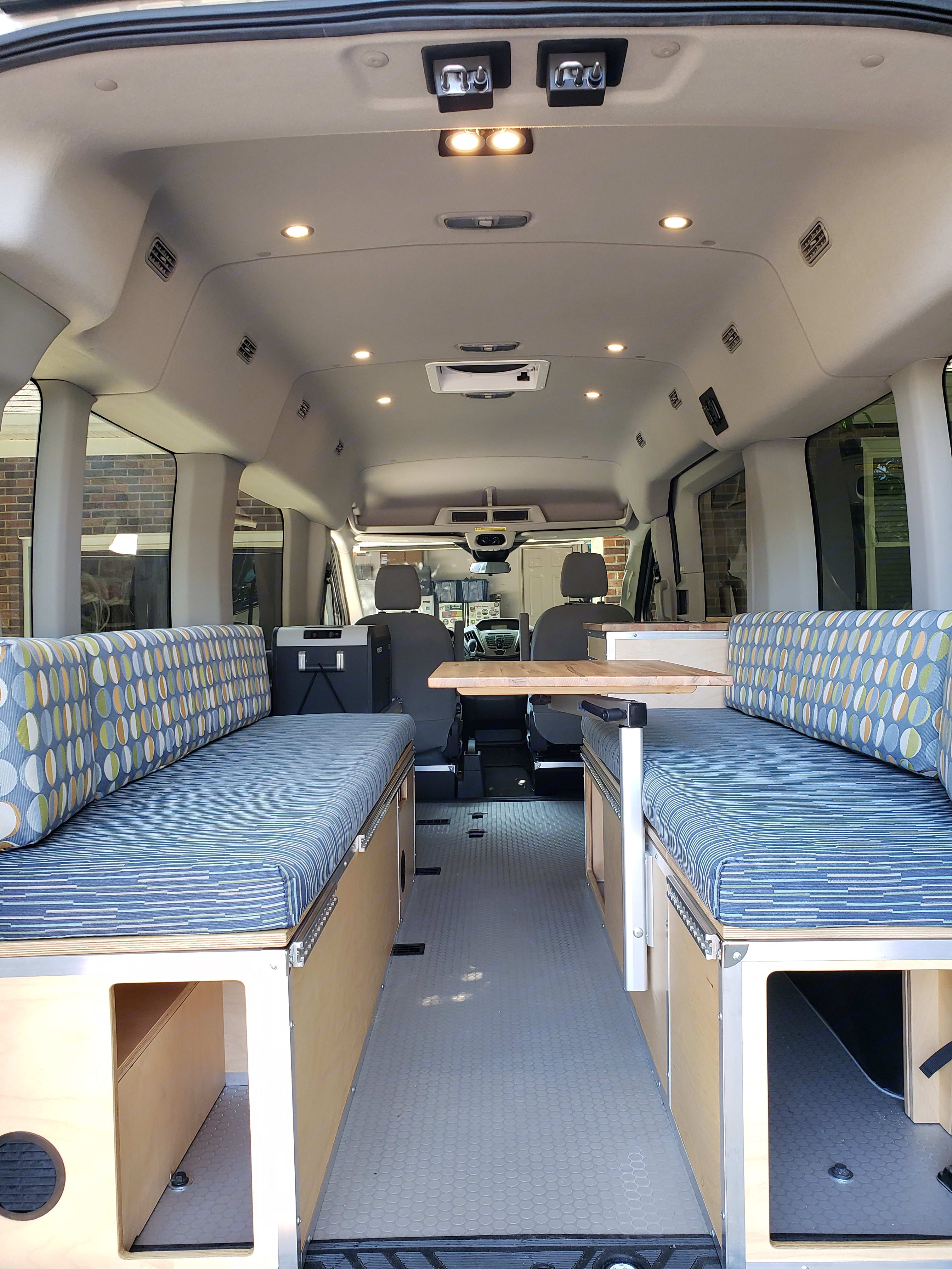 Rear View - Bench seats with storage below, converts to queen size bed.  Swivel lagun table.. Ford Transit 2016