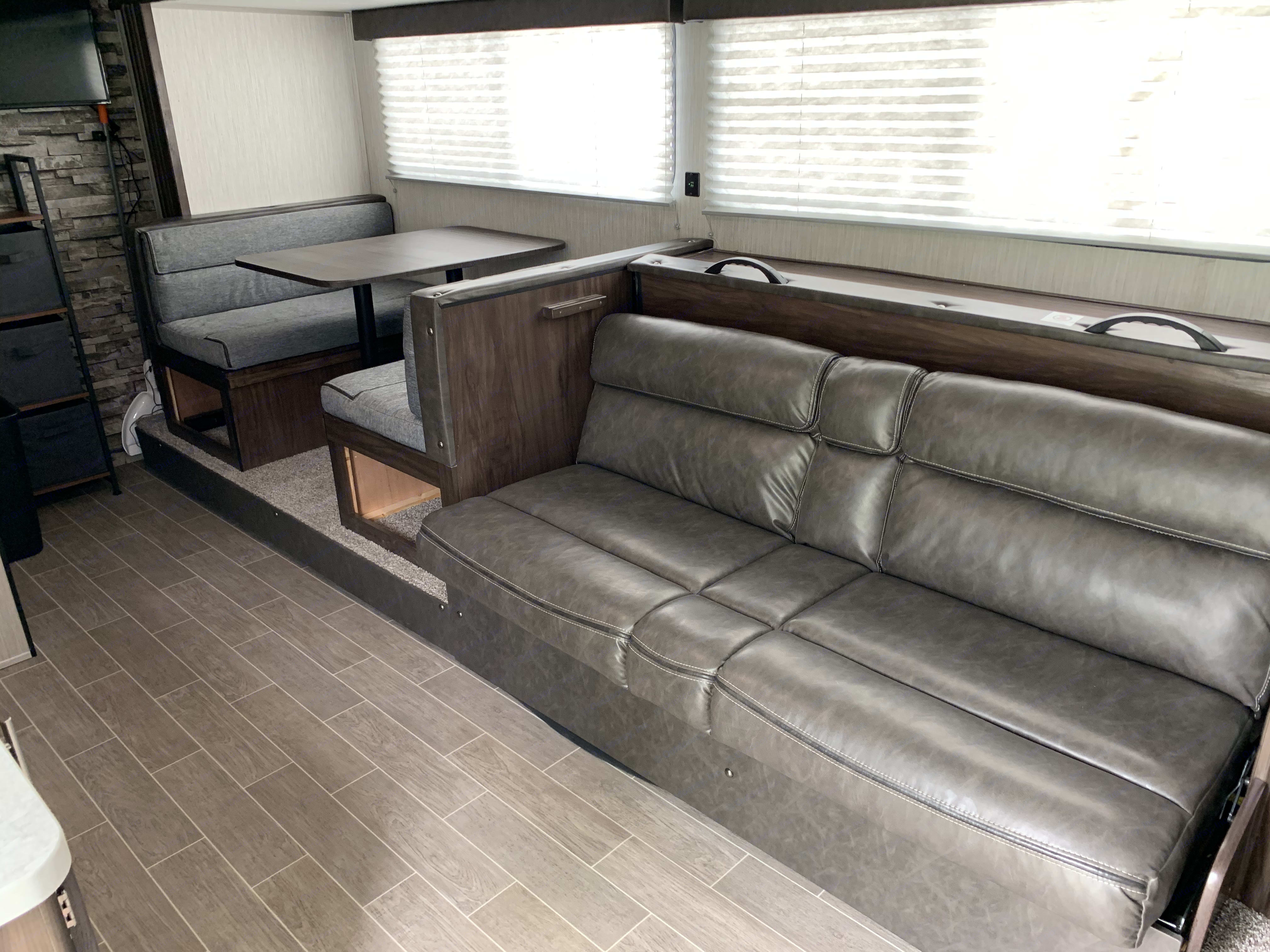 Interior slide. Sofa and dinette. Forest River Cherokee Wolf Pup 2020