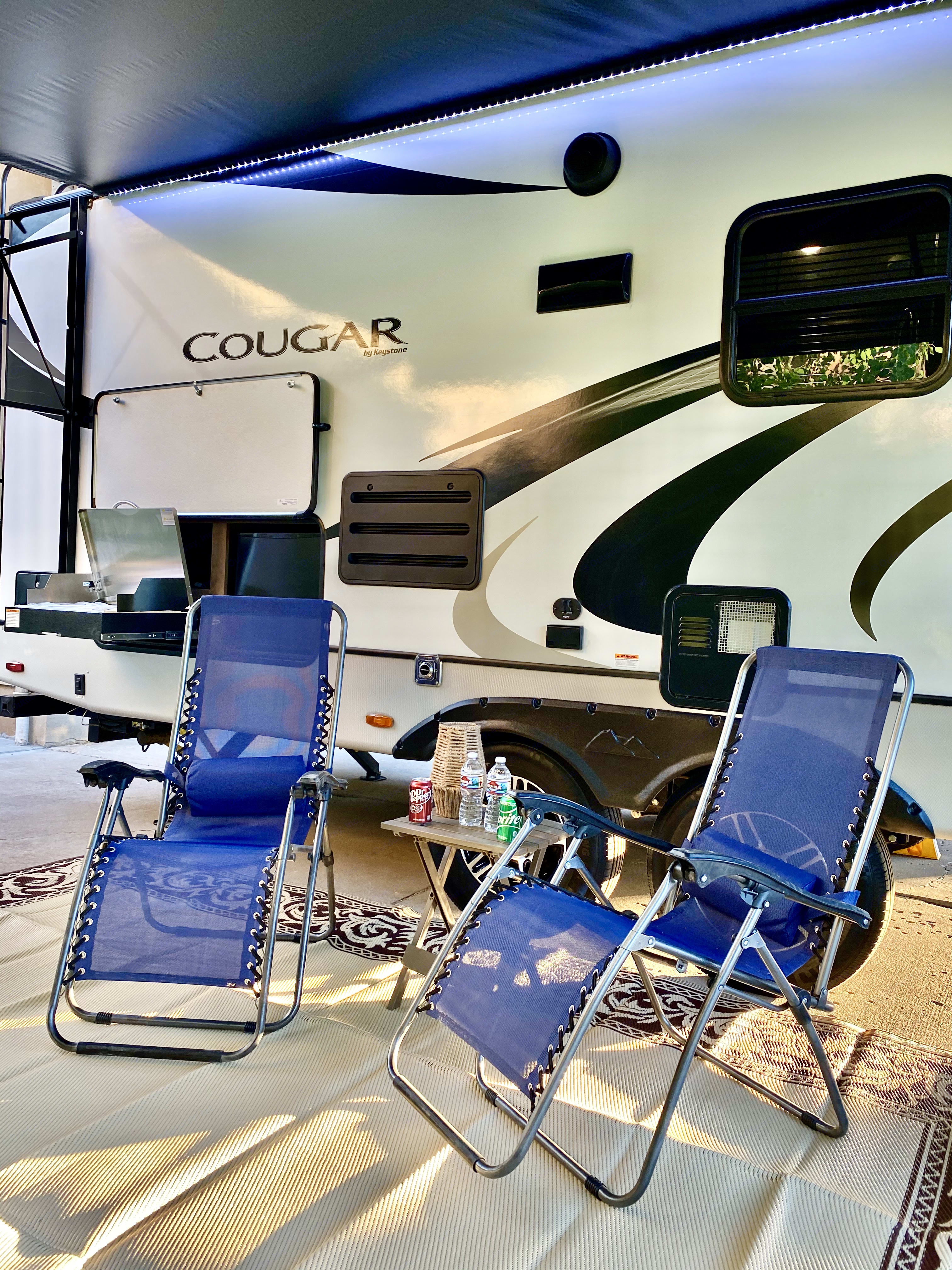 Zero Gravity Chairs Set Up Next To The Outdoor Grill and Fridge Underneath LED Lit Awning. Keystone CougarHalf-Ton 2020