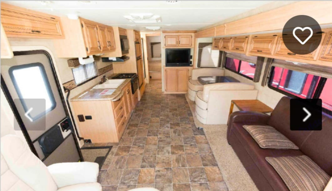 Living room, dinette, kitchen with slide out roomfully extended. Thor Motor Coach Four Winds 2011