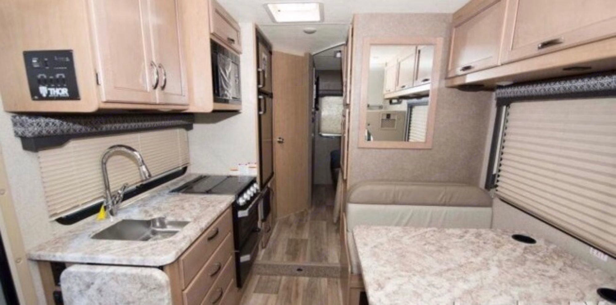 table folds into a bed , 3 burner stove and sink with tons of overhead storage , electrical outlets and usb. Thor Motor Coach Four Winds 2020