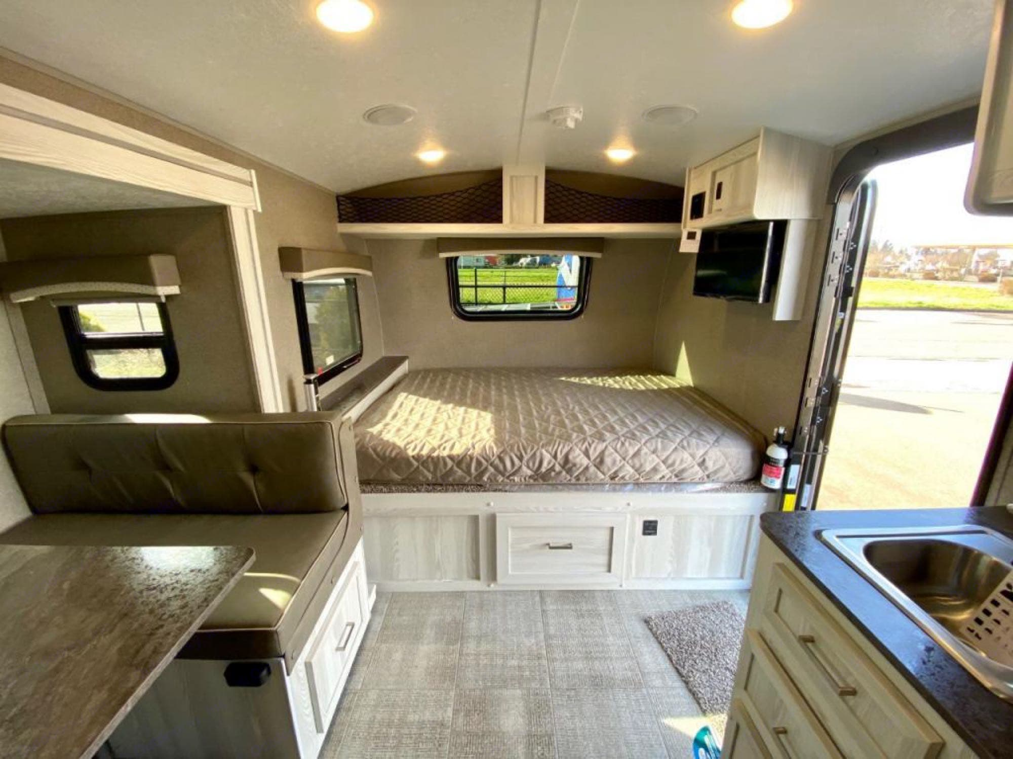 Queen bed with storage under and over, TV w/DVD on angle bracket. Forest River Rockwood 2021