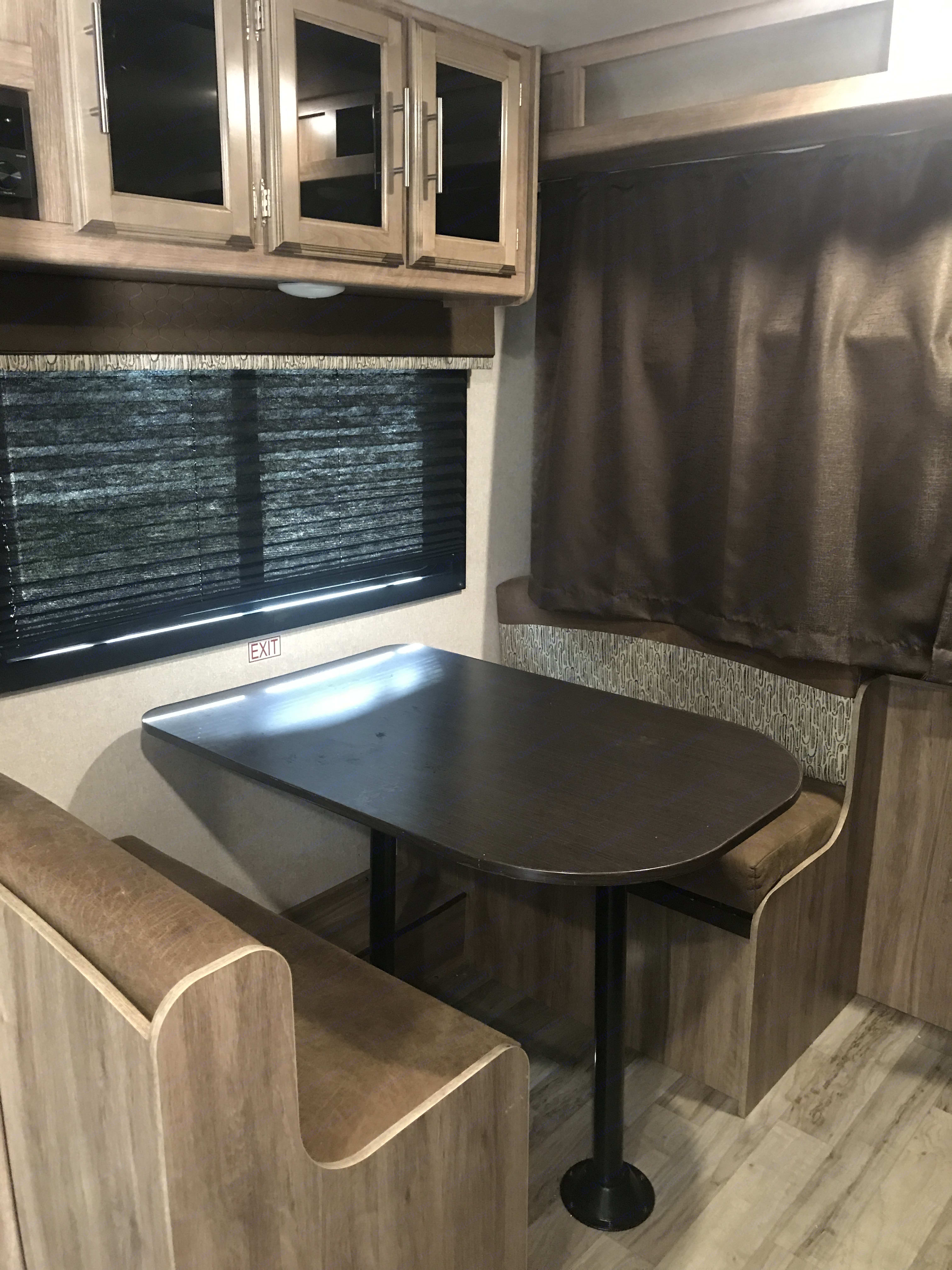 Dining space with storage above. Table drops to convert to a bed. Or remove and a port-a-crib fits between the seats!. Jayco Jay Feather 2018