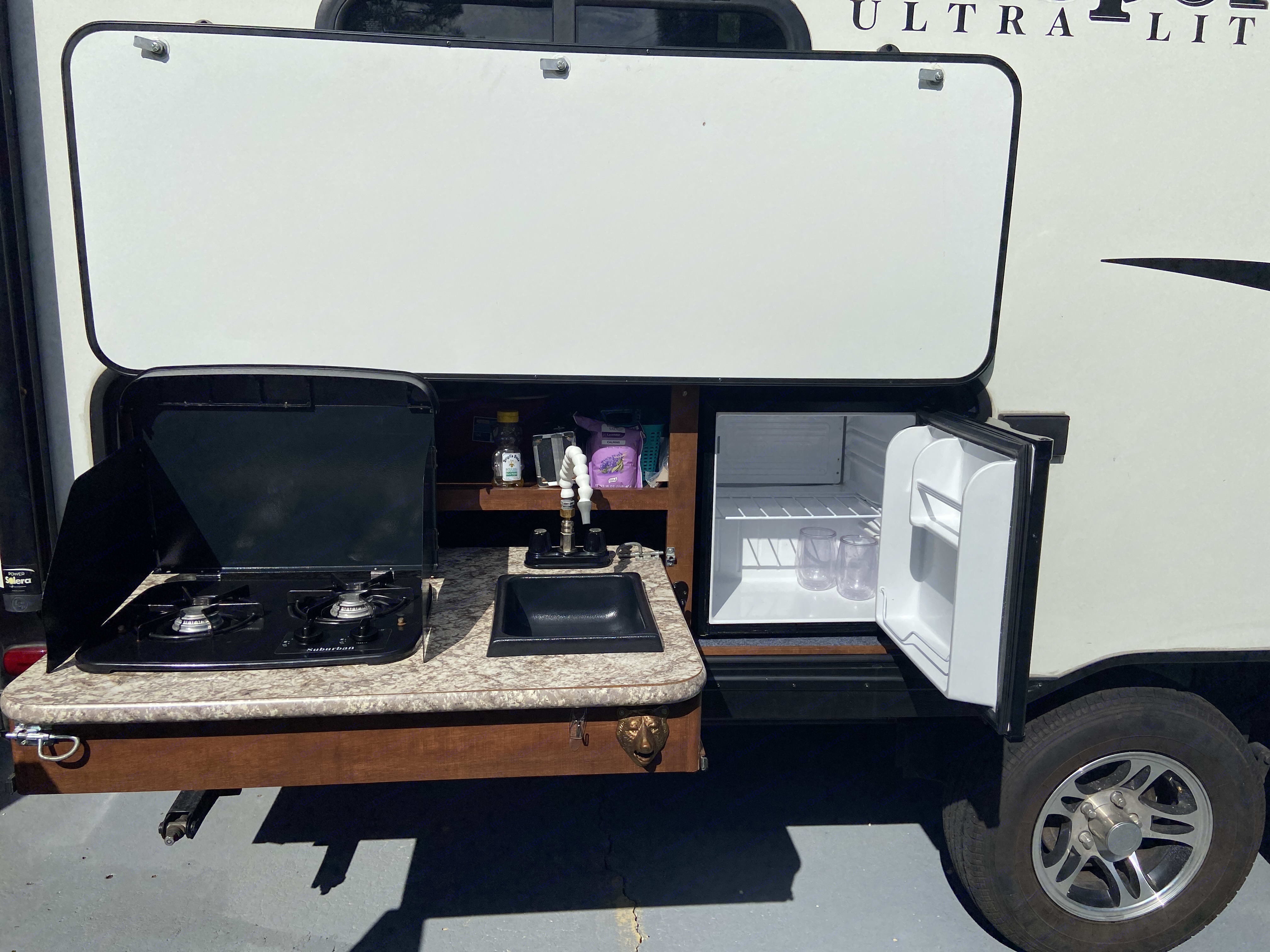 Outdoor kitchen w/ 2 burner gas stove, sink, storage & fridge. Oh, & bottle opener of course.2 exterior outlets too (fan,speaker,lights). Keystone Passport 2018