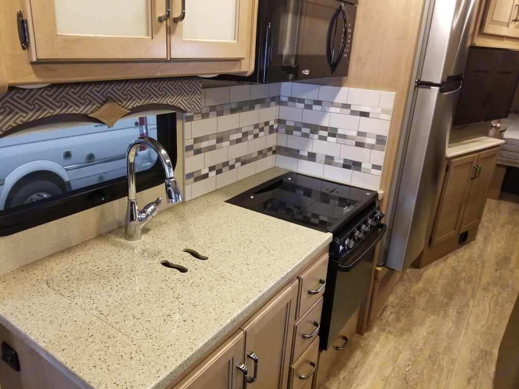 Kitchen with matching sink covers, microwave, 3 burner stove and gas oven. Thor Motor Coach Hurricane 2018