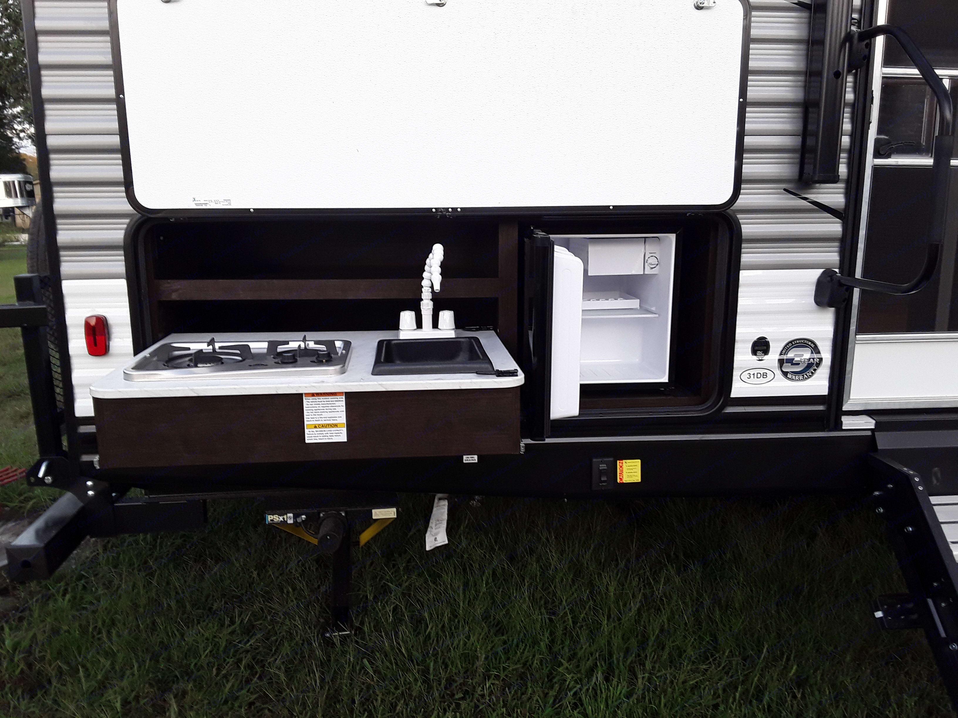 outdoor kitchen: stove, sink, and fridge/freezer. Heartland Trail Runner 2021