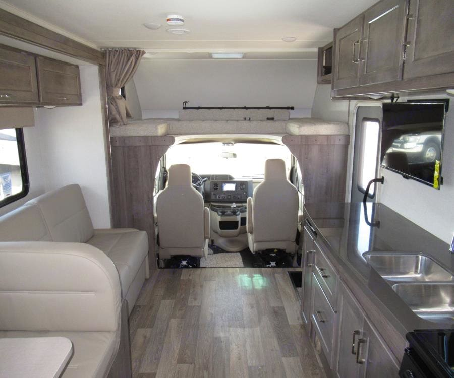Shot from kitchen towards driving cabin- shows sleeping bunk above driving cabin.. Winnebago Minnie Winnie 2020