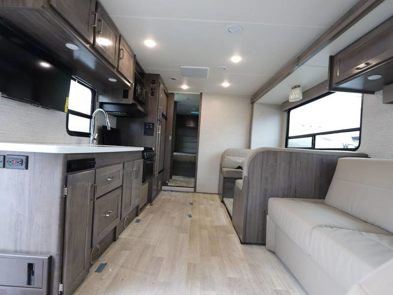 Shot from driving cab towards back- shows kitchen and jack knife sofa. Winnebago Minnie Winnie 2020