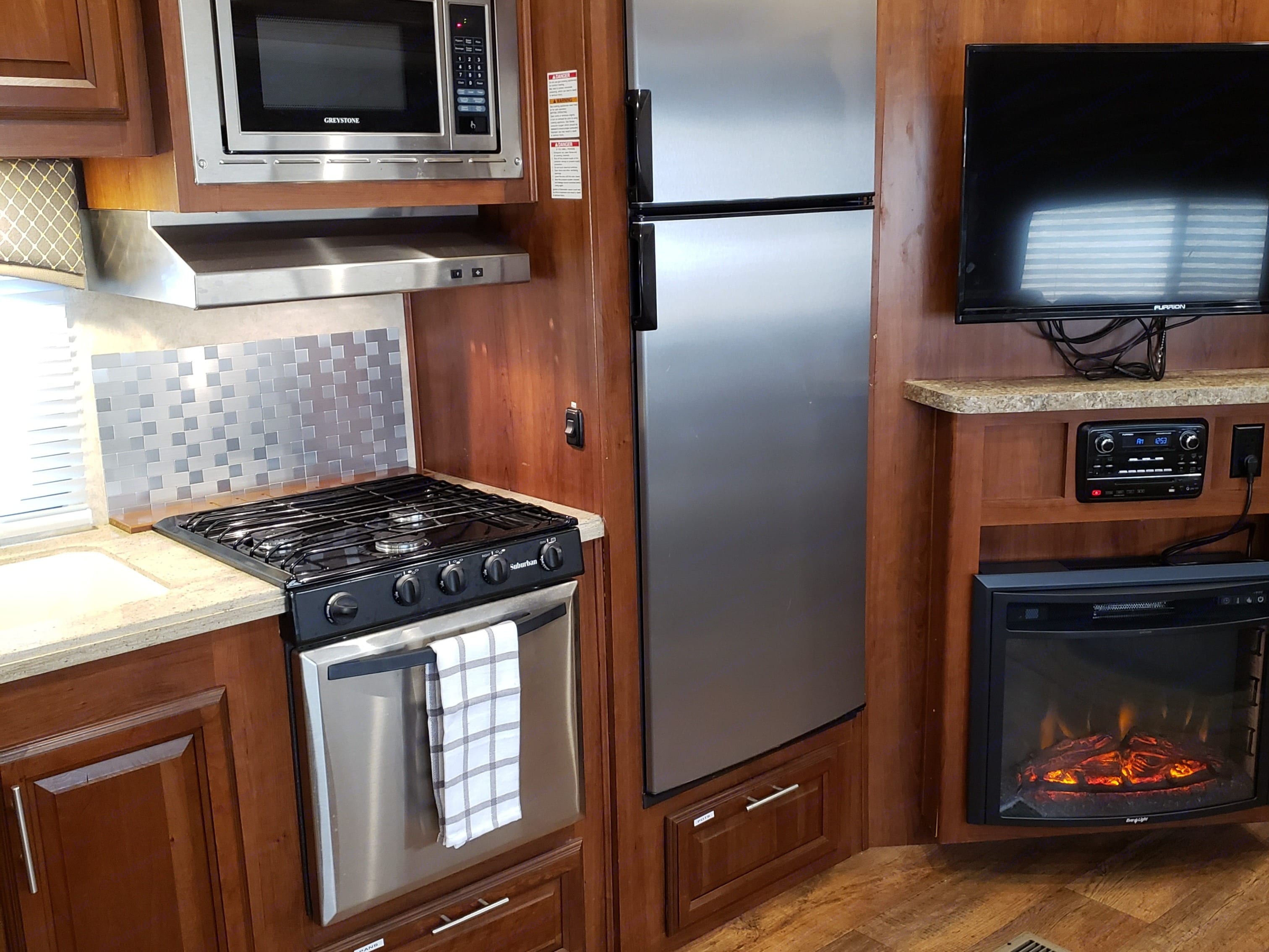 Kitchen with large TV and fireplace that does heat.. Forest River Wildcat 2015
