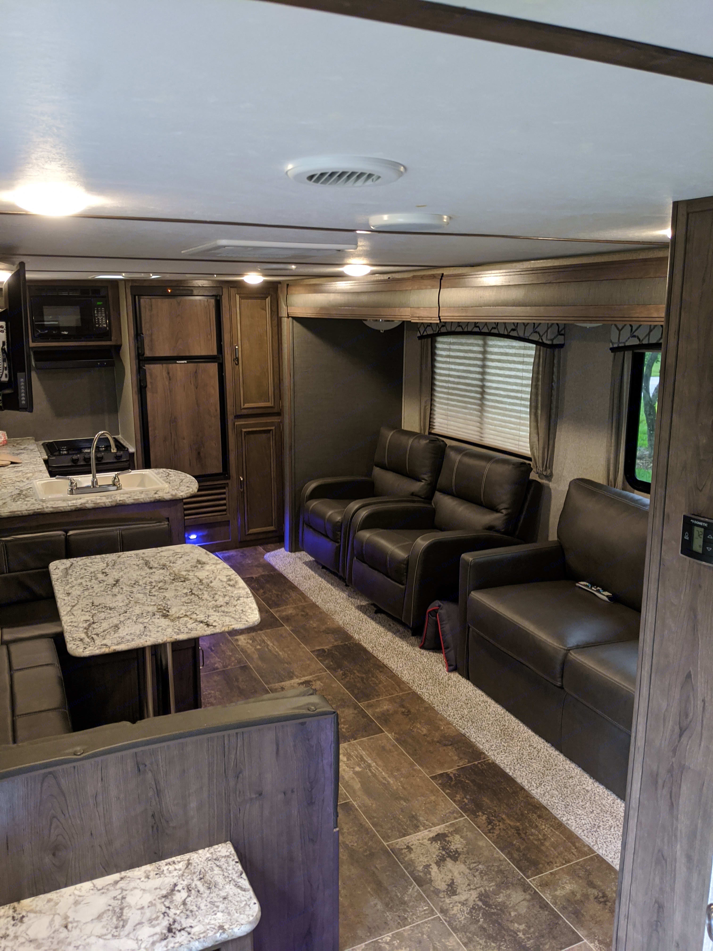 Living Area with full Kitchen, 2 chairs, pull out sofa, and dinette that converts to a bed.. Keystone Passport 2018