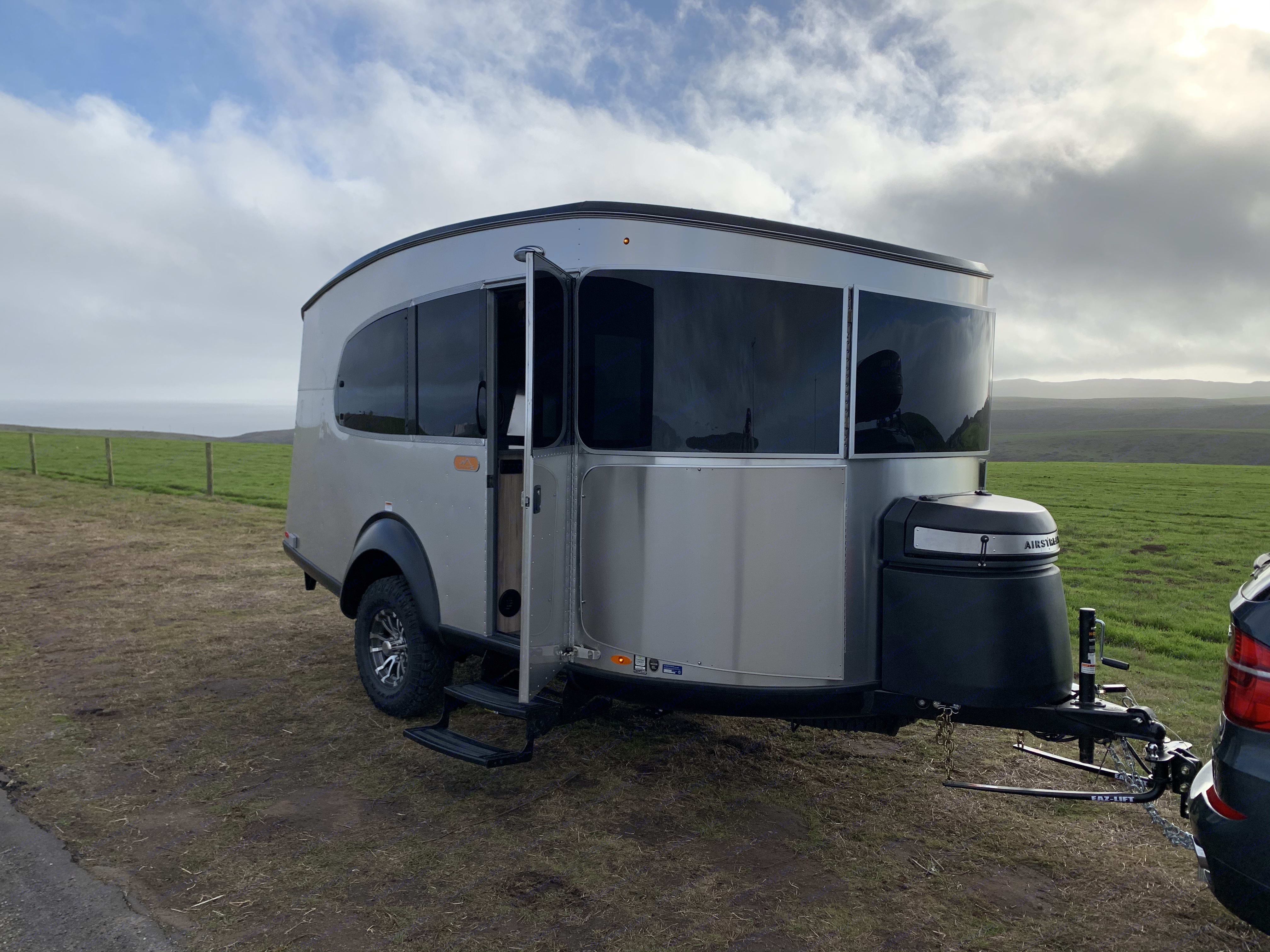 Main entrance on the curbside with 2 20lb propane tanks in the front.. Airstream Basecamp 20X 2021