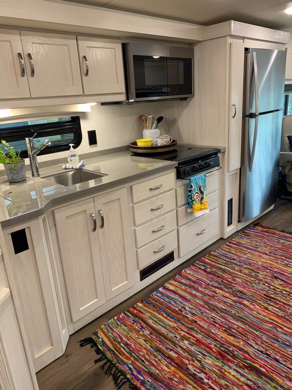 The kitchen has an apartment size refrigerator and plenty of cabinet AND counter space!. Winnebago Forza 2020