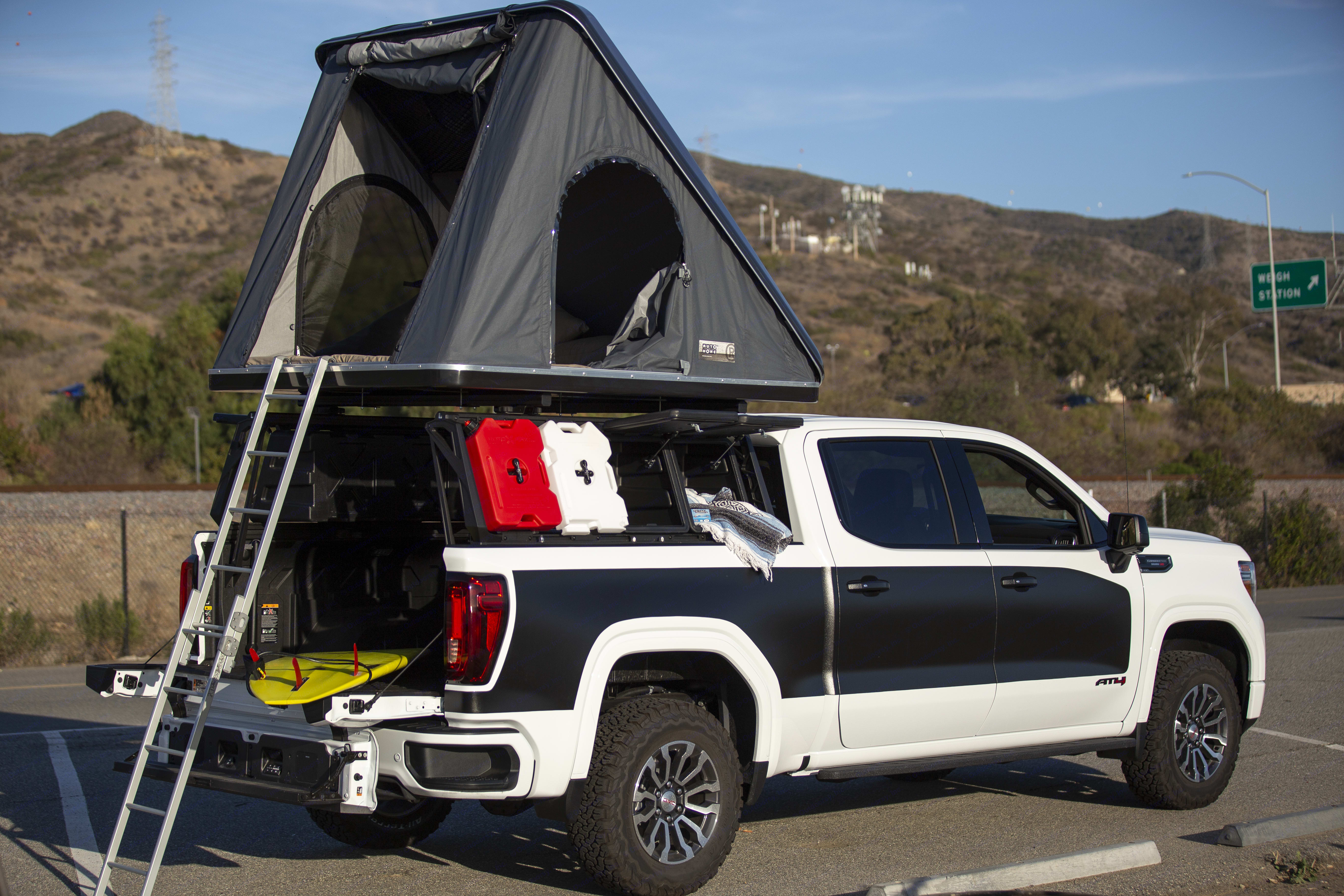 Two smaller locking storage compartments are shown open with roto-pax 2 gal. gas and water containers at back of rack. . GMC Sierra 1500 AT4 Duramax Diesel 2021