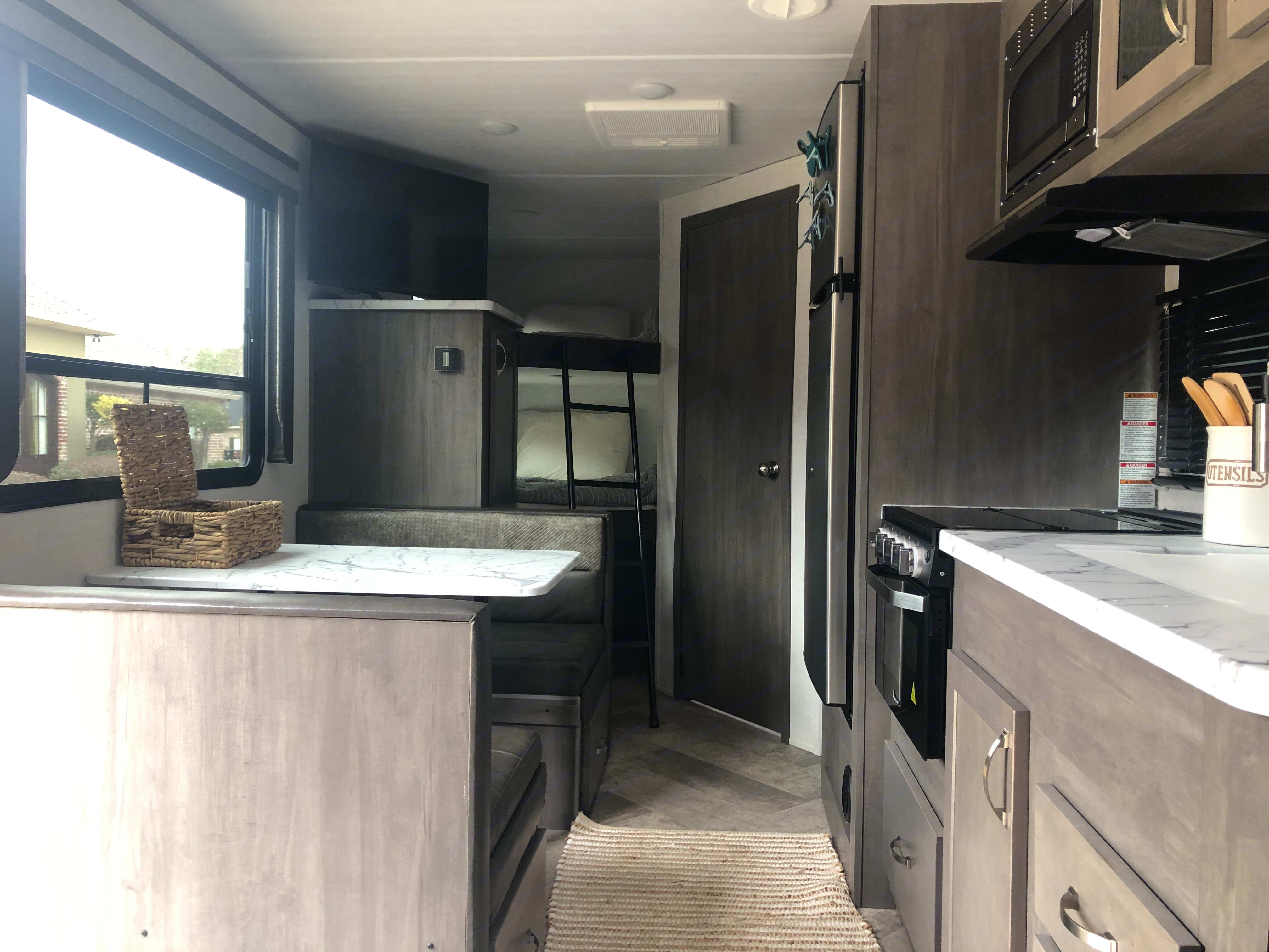 Kitchen with dinette (converts to bed), farmhouse style sink with flexible faucet, full fridge, 3 burner gas stove, and gas oven. Forest River East to West Alta 2021