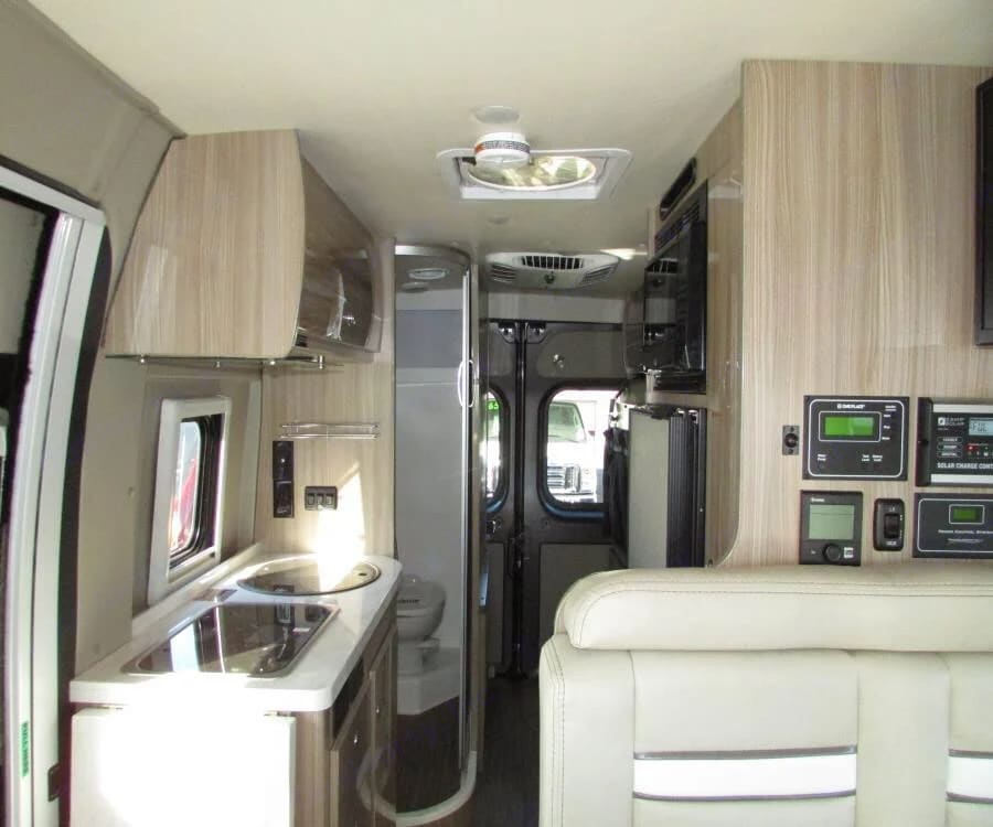 Corian countertops, white leather seats, light wood cabinets and light colored vinyl flooring. Refrigerator and Freezer just behind the dinette seat. Winnebago Travato 2020