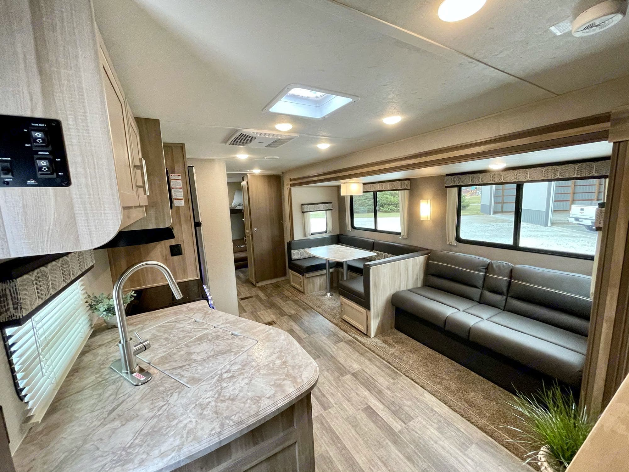 living area/kitchen. u-shaped dinette, gas stove, oven, microwave. Coachmen Catalina 303QBCK 2021
