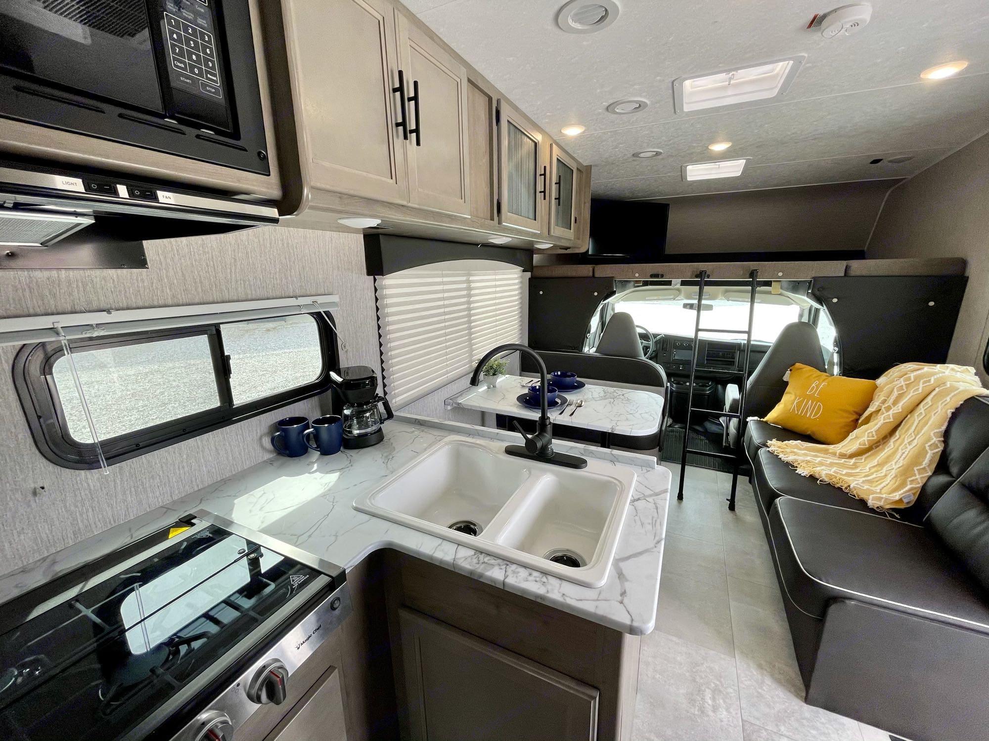 kitchen- gas stove, microwave, farmhouse sink. Coachmen Freelander 27QB 2021