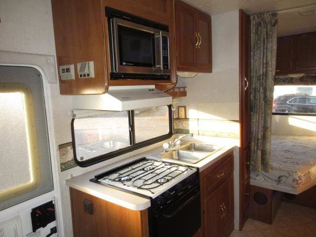 Stainless steel sink, microwave, 3 burner stove, hood with fan and light. Coachmen Catalina 2002