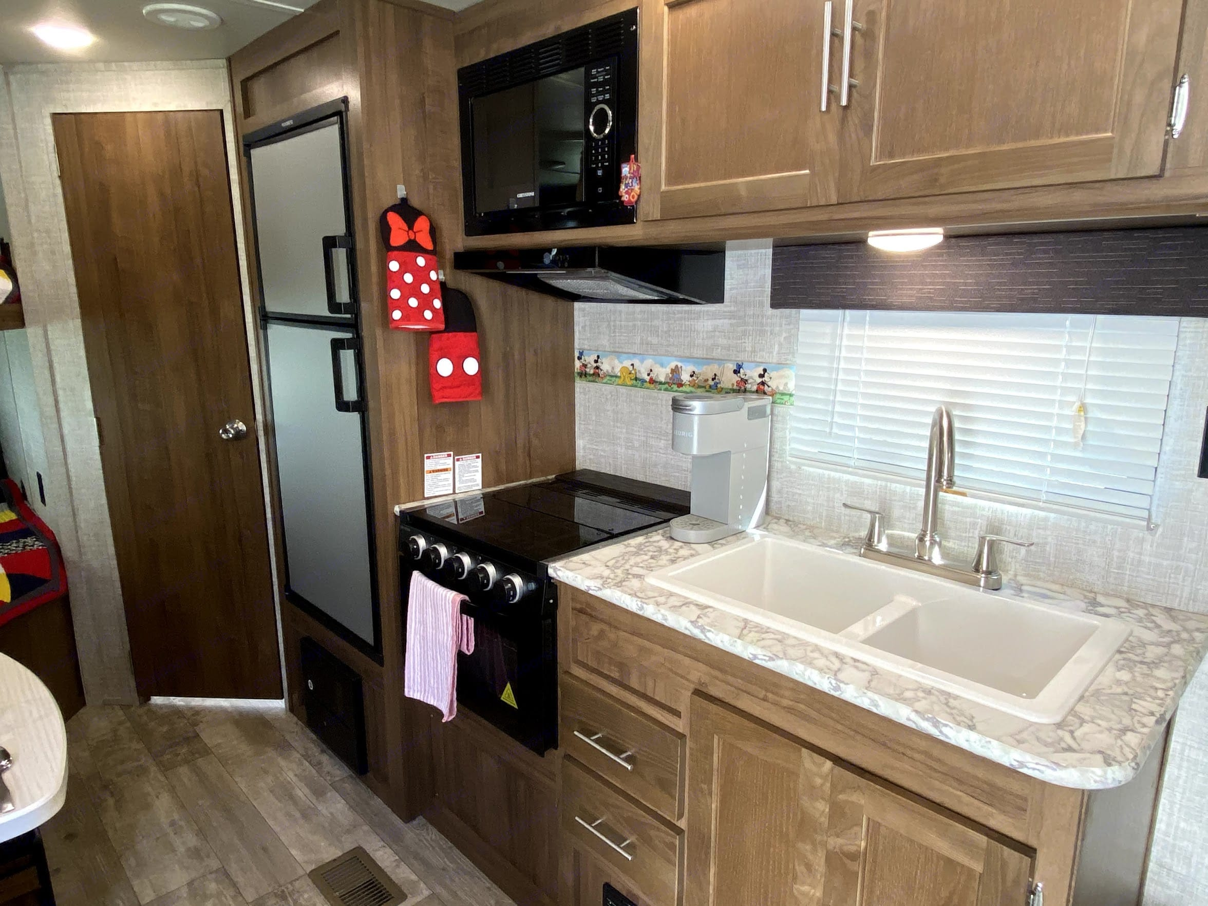 Kitchen includes refrigerator with freezer, 3-burner stove, oven, microwave and split sink. A Keurig is also included!. Gulf Stream Innsbruck 2020