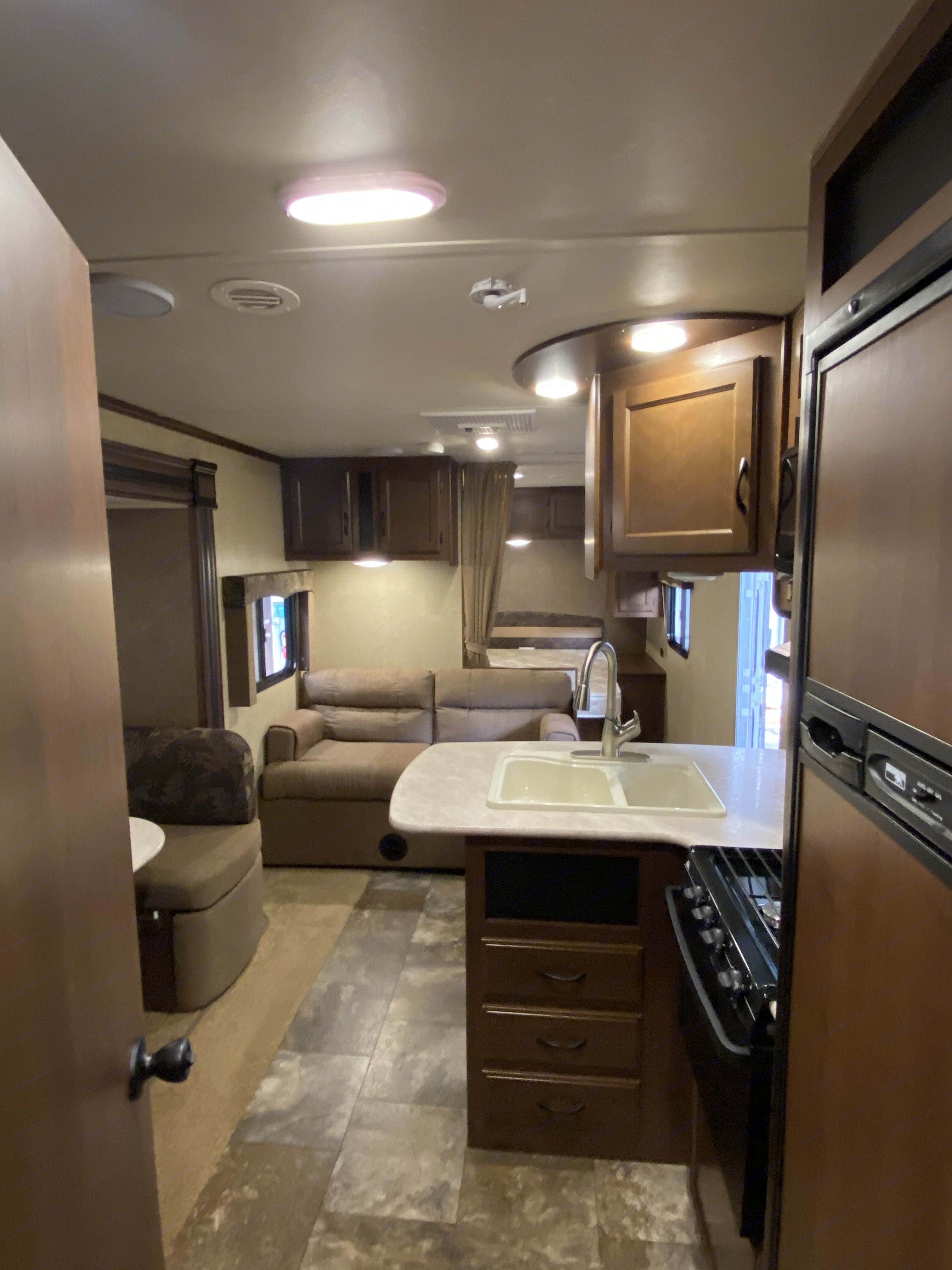 View from kitchen of island, fridge (with freezer), stove, cupboard and futon sofa. . Jayco Camper Trailer- Swift 2014