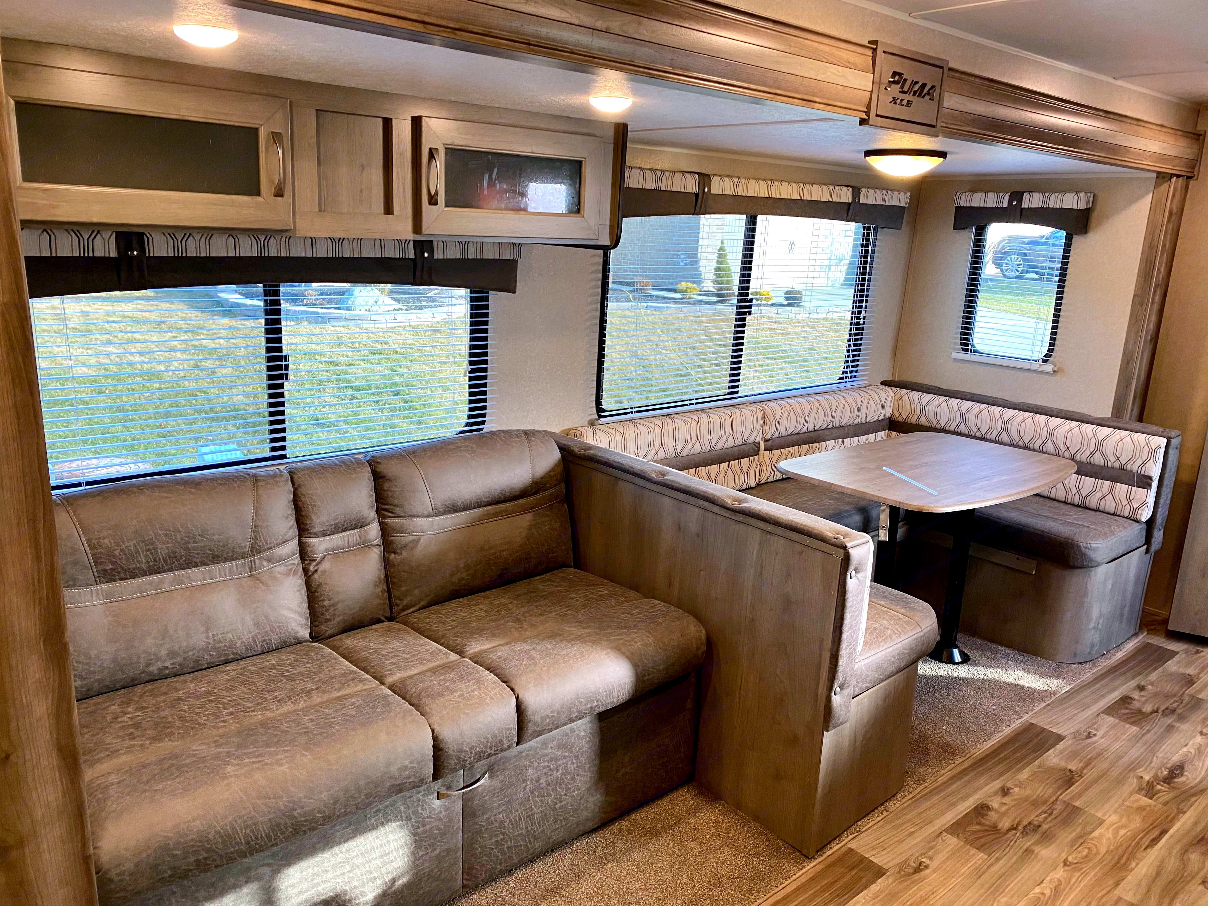 Dinette and Sofa with slide open. Forest River Puma XLE Lite 27RBQC 2019