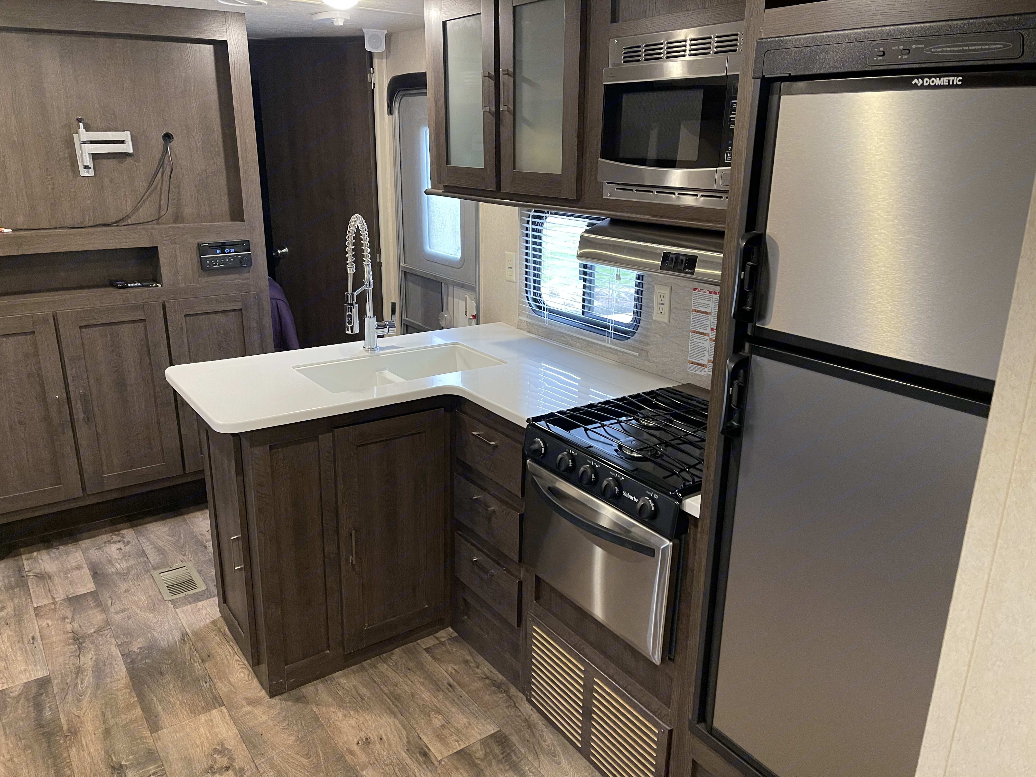 Flat screen TV across from reclining couch, surround sound, DVD player and residential sink.. Forest River Wildwood 31KQBTS 2018