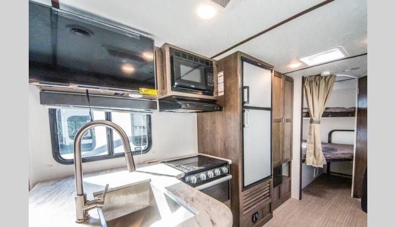 kitchen, flat screen, stove, oven, microwave. fridge pantry and storage space. Keystone Passport 2021