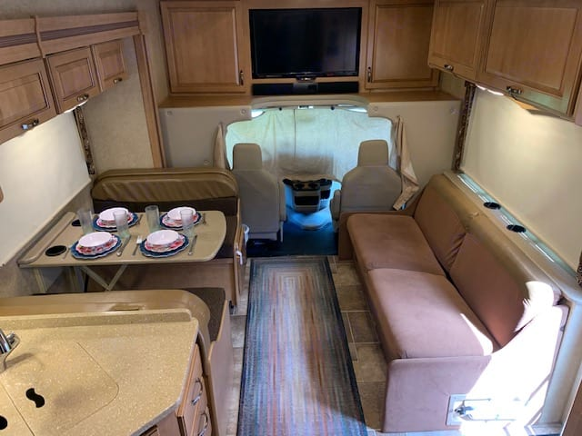 Plenty of room to enjoy your meals or relax.  The entertainment system includes a DVD player and a TV that can connect to your device.. Thor Motor Coach Four Winds 2015