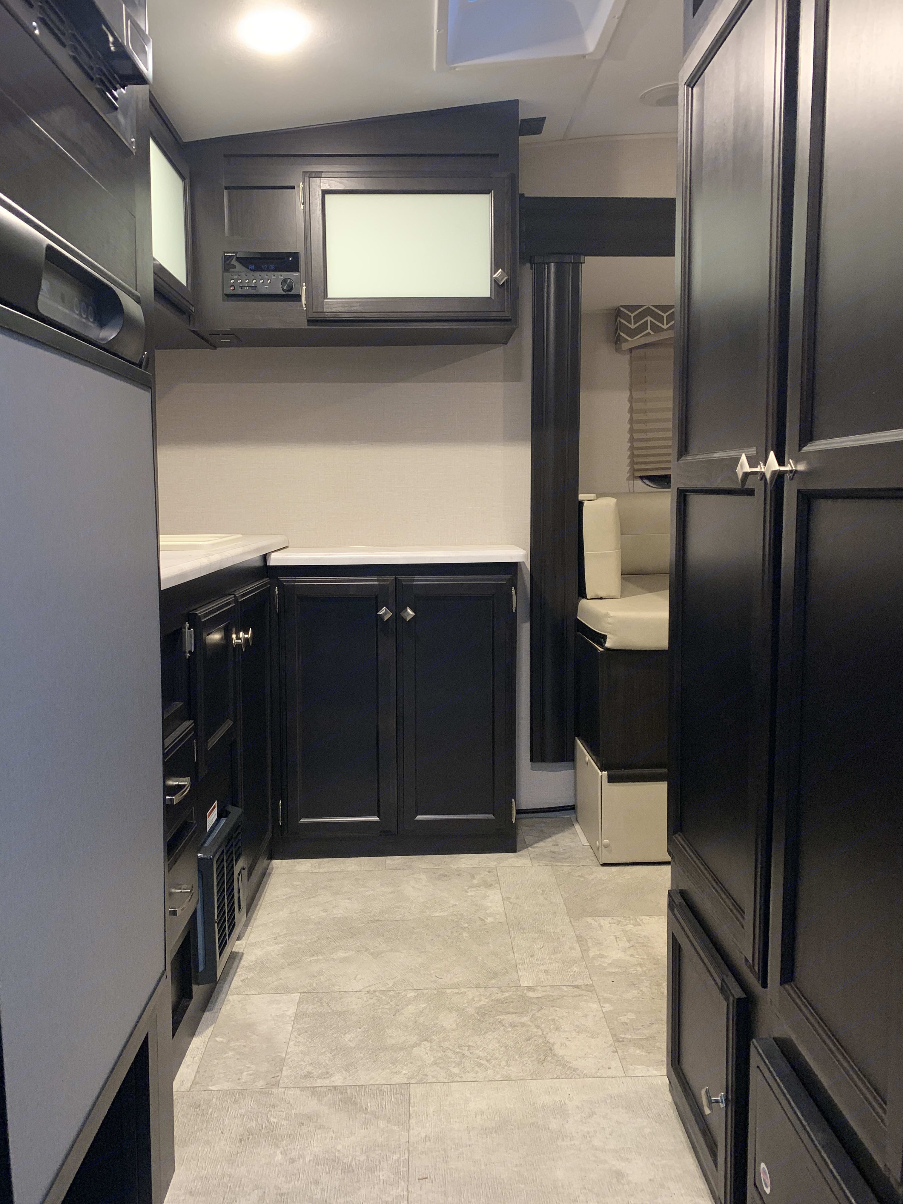 Walking into camper, immediate left is refrigerator, right is closet and pantry, ahead is wrap around cabinets and countertops.. Venture Rv Sonic 2019