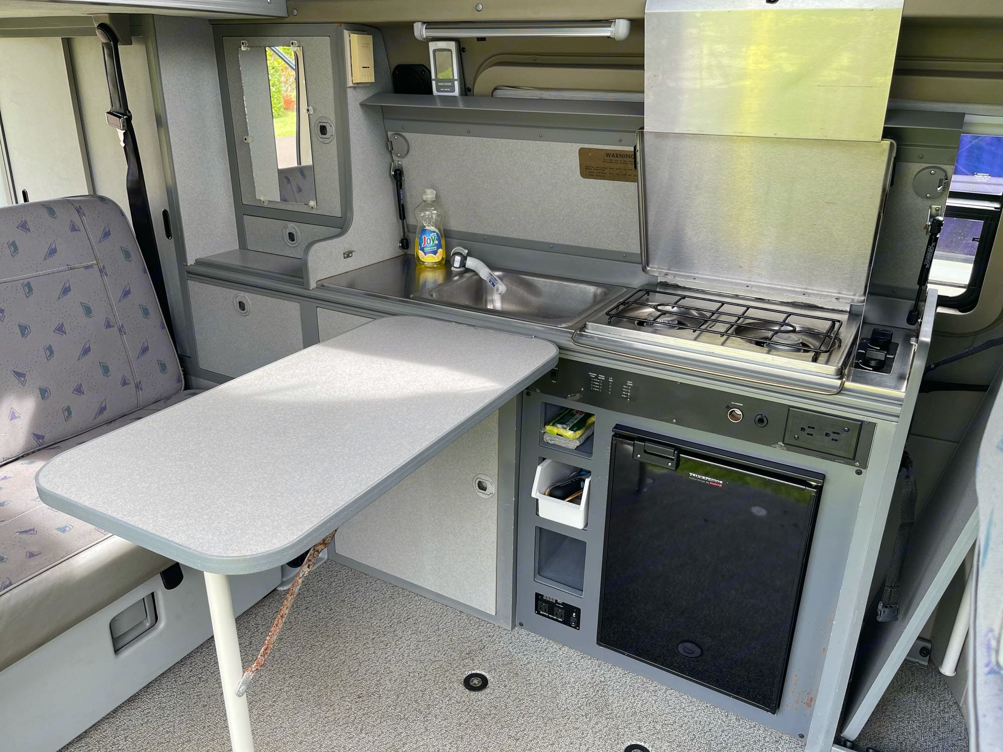 with the two tables to the right of the stove, you can convert your kitchen into a comfy place to eat, the second table fits over the fridge so you can spin the captain's seats around and have a table for four!. Volkswagen Eurovan Full Camper 1997