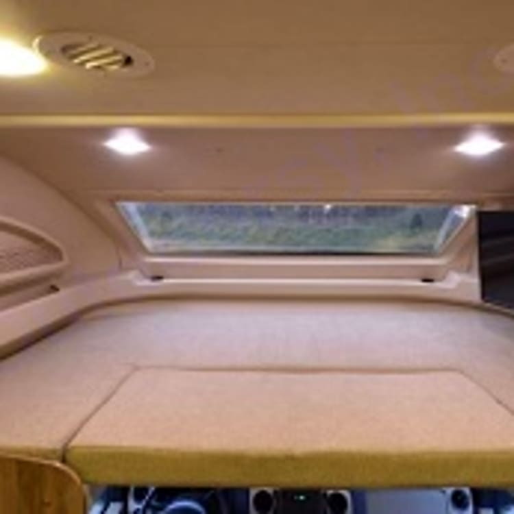 Top cab sleeping area with tv and panoramic window with power shades.