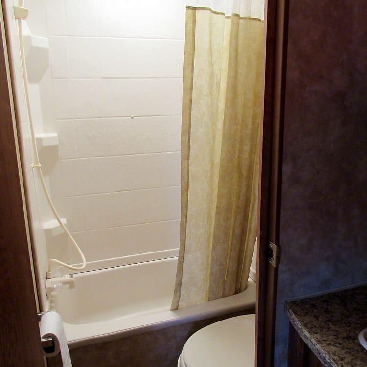 The bathroom has a tub/shower combo.