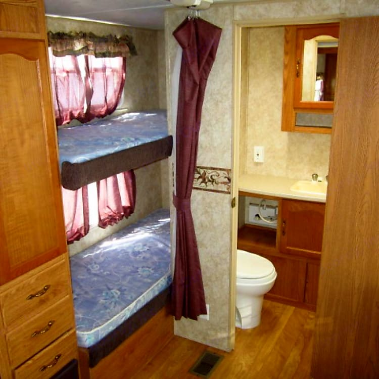 Each bunk bed has its own window that opens, avoiding a claustrophobic, stuffy feeling. Each has its own reading light as well. The bunks go fairly deep into the back of the trailer, so younger children are pretty safe from falling out, as they can be tucked in, pretty far to the back. There is a privacy curtain to draw at bedtime. Memory foam mattresses have been added to the original mattresses, making the beds very comfortable. Both beds have mattress covers on them for your protection. Just bring your own bedding/sleeping bag and pillow. The bunks are the length of a twin bed, but narrower than a twin. However, twin sheets work fine on these beds.
