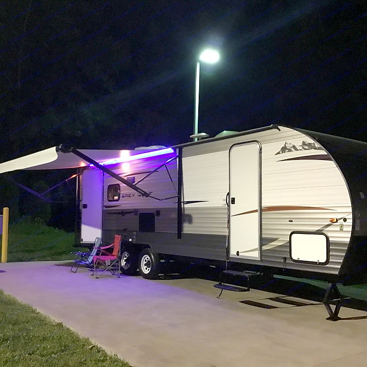 Trailer at night with the patio awning open and fluorescent lights on.