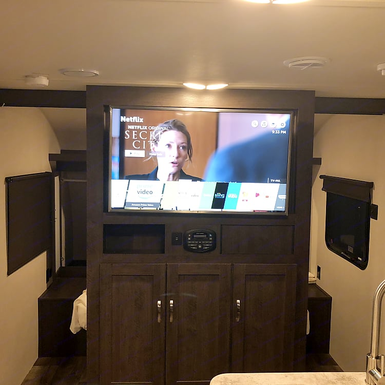 Entertainment center with storage underneath. Queen bed with solid slide out doors instead of curtains is behind it!