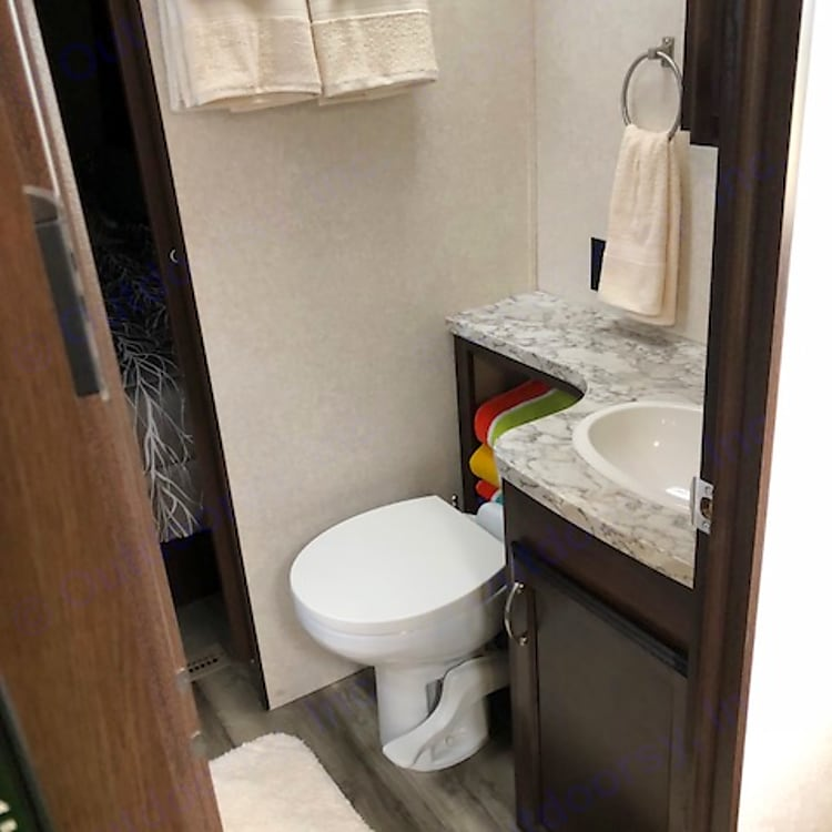 Rooming bathroom. Soap, towels, toilet paper, and toilet brush.