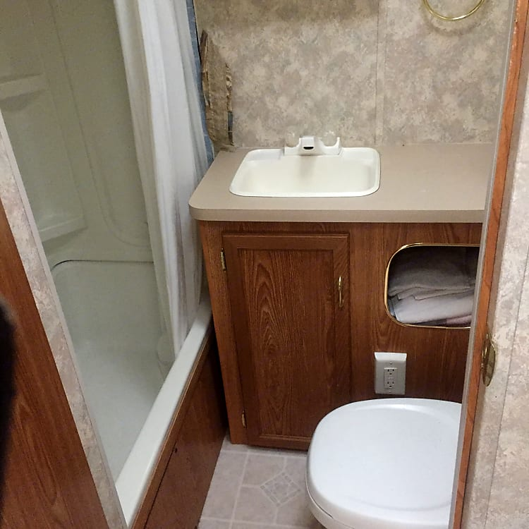 Sink and tub shower in bathroom located conveniently in rear of unit