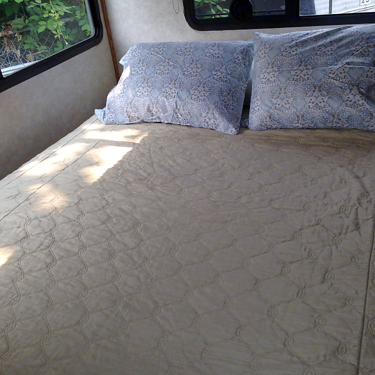 Queen bed with Sealy Posturpedic mattress and supplied linens.