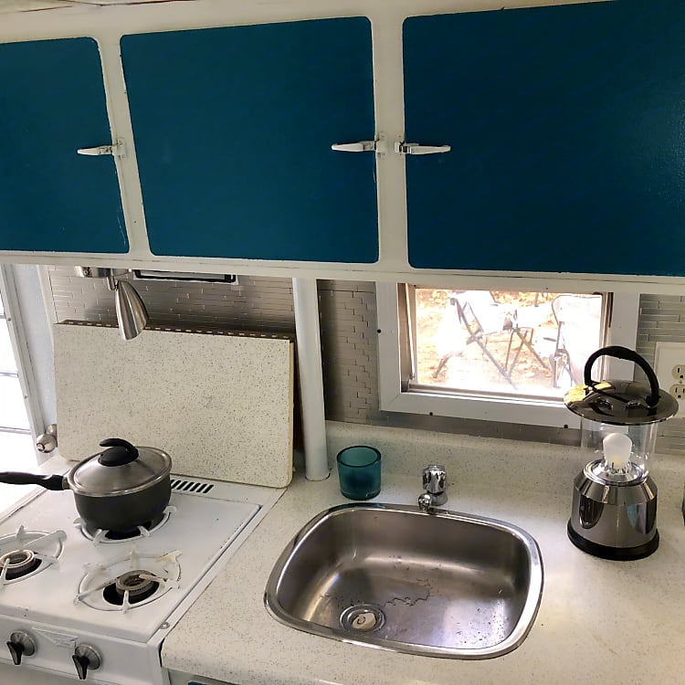 Fully outfitted kitchen with propane stove and sink.